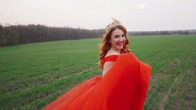 La mujer joven en un vestido rojo lujoso corre a lo largo del campo verde y sonríe almacen de video