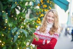 La mujer joven en una calle de París adornó para la Navidad Imagenes de archivo