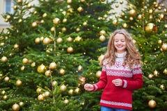La mujer joven en una calle de París adornó para la Navidad Foto de archivo