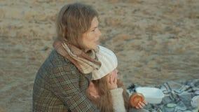 La mujer joven en una capa con una muchacha con el pelo rizado, madre con la hija, en la playa por el río, océano, tenía una comi almacen de metraje de vídeo