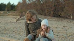 La mujer joven en una capa con una muchacha con el pelo rizado, madre con la hija, en la playa por el río, océano, tenía una comi almacen de video