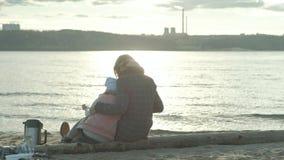 La mujer joven en una capa con una muchacha con el pelo rizado, madre con la hija, en la playa por el río, océano, tenía una comi metrajes