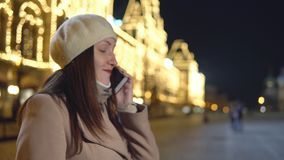 La mujer joven en una capa no es el hablar cuadrado en el teléfono almacen de video
