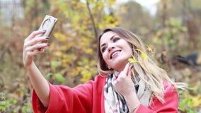 La mujer joven en una capa roja y la bufanda con un teléfono celular en un otoño parquean almacen de metraje de vídeo