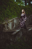 La mujer joven en una escalera en la madera Fotos de archivo libres de regalías