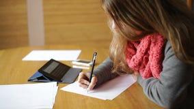 La mujer joven en una oficina da la escritura en el papel metrajes