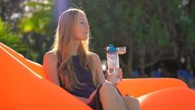 La mujer joven en una playa tropical se sienta en un sofá inflable y bebe el agua de una botella plástica usable multi bebida metrajes