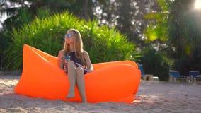 La mujer joven en una playa tropical se sienta en un sofá inflable y bebe el agua de una botella plástica usable multi bebida almacen de video