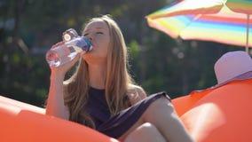 La mujer joven en una playa tropical se sienta en un sofá inflable y bebe el agua de una botella plástica usable multi bebida almacen de metraje de vídeo