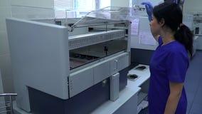La mujer joven en uniforme azul y los guantes de goma abre la puerta de la máquina de trabajo en el laboratorio y parecer interio metrajes