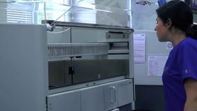 La mujer joven en uniforme azul y los guantes de goma abre la puerta de la m?quina de trabajo en el laboratorio y parecer interio almacen de video