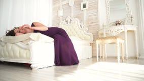 La mujer joven en vestido de noche miente en una cama blanca y sueños almacen de metraje de vídeo