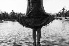 La mujer joven en vestido está presentando de una manera linda, mientras que se coloca en el agua imágenes de archivo libres de regalías
