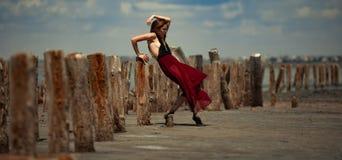La mujer joven en vestido largo está bailando en arena en fondo de la playa Foto de archivo