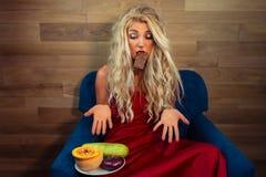 La mujer joven en vestido rojo elegante se sienta en la butaca con el chocolate en dientes foto de archivo