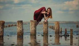 La mujer joven en vestido rojo está bailando en agua en fondo del mar fotos de archivo libres de regalías