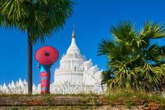 La mujer joven en vestido tradicional está mirando una pagoda cerca de la ciudad antigua de Mandalay, Myanmar imagenes de archivo