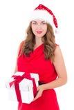 La mujer joven en vestido y el sombrero rojos de santa con el regalo de Navidad es Imagenes de archivo