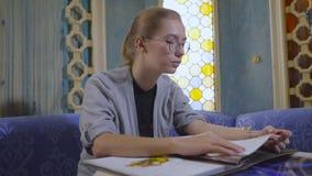 La mujer joven en vidrios está moviendo de un tirón a través del menú en un restaurante asiático metrajes