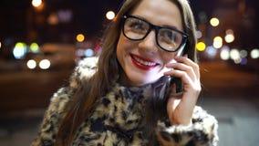 La mujer joven en vidrios usando smartphone en ciudad de la noche enciende el fondo almacen de video