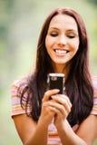 La mujer joven encantadora lee sms Imágenes de archivo libres de regalías