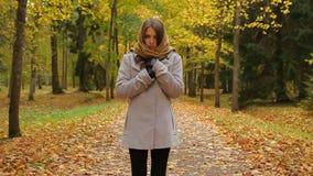 La mujer joven encantadora se coloca y tiembla de frío en un parque del otoño almacen de metraje de vídeo