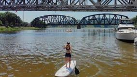 La mujer joven encendido se levanta el tablero de paleta en el río almacen de video