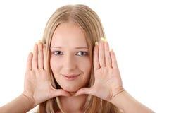 La mujer joven enmarca su cara con las manos foto de archivo