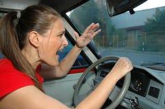 La mujer joven enojada conduce un coche Imágenes de archivo libres de regalías