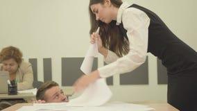 La mujer joven enojada nerviosa del retrato dobló el papel bajo la forma de cuerno y la griterío en el hombre que sentándose deba almacen de video