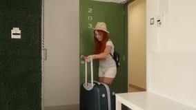 La mujer joven entra con su maleta en su nuevo apartamento metrajes