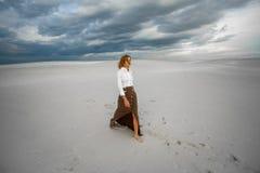 La mujer joven entra descalzo en desierto en fondo del cielo Imagen de archivo libre de regalías