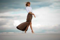 La mujer joven entra descalzo en desierto en fondo del cielo Vista lateral Fotos de archivo