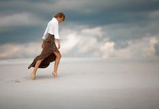 La mujer joven entra descalzo en desierto en fondo del cielo Vista lateral Fotos de archivo libres de regalías
