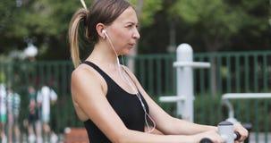 La mujer joven entra para los deportes en el parque en el simulador metrajes
