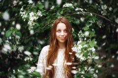 La mujer joven entre la primavera florece al aire libre Imagenes de archivo