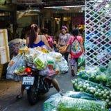 La mujer joven entrega docenas de paquetes atados con correa sobre su vespa a un mercado chino en Banmgkok Imagen de archivo libre de regalías