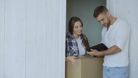 La mujer joven entrega la caja de cartón al cliente en casa El hombre firma adentro el tablero para recibir el paquete almacen de metraje de vídeo