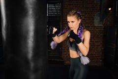 La mujer joven entrena en ring de boxeo con el saco de arena pesado Fotografía de archivo libre de regalías