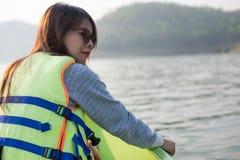 La mujer joven equipa la relajación que se sienta del chaleco salvavidas en proa ella mira Fotografía de archivo