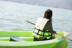 La mujer joven equipa la relajación que se sienta del chaleco salvavidas en proa tiene el PED Fotos de archivo