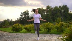 La mujer joven es cuerda de salto en el parque A cámara lenta almacen de video