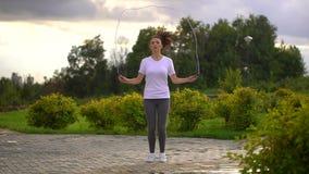 La mujer joven es cuerda de salto en el parque A cámara lenta metrajes