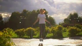 La mujer joven es cuerda de salto en el parque A cámara lenta almacen de metraje de vídeo
