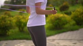 La mujer joven es cuerda de salto en el parque Ciérrese para arriba de sus pies y nalgas A cámara lenta almacen de video