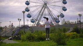 La mujer joven es cuerda de salto en el parque en el fondo de la noria A cámara lenta metrajes