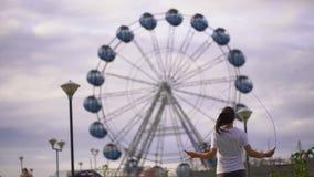 La mujer joven es cuerda de salto en el parque en el fondo de la rueda de Ferris 4 k almacen de video