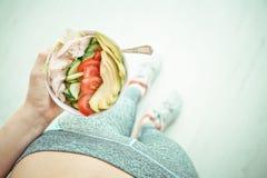 La mujer joven es de reclinación y de consumición de una ensalada sana después de un entrenamiento Fotos de archivo libres de regalías
