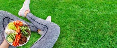 La mujer joven es de reclinaci?n y de consumici?n de una comida sana despu?s de un entrenamiento imagen de archivo