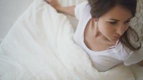 La mujer joven es el despertar, mintiendo en cama en dormitorio en mañana soleada metrajes